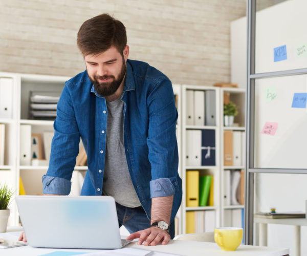 Portrait of bearded entrepreneur standing at desk in modern office looking at laptop screen and smiling while planning project