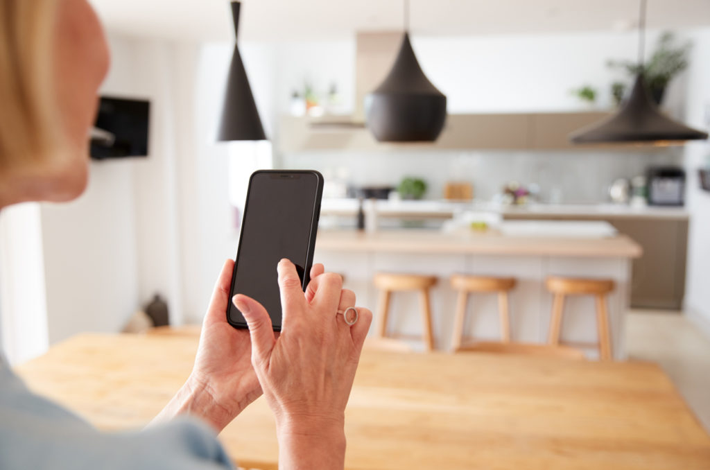 Mature Woman Using App On Mobile Phone To Control Central Heating Temperature In House